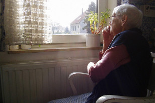 elderly gazing out window